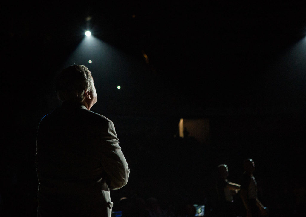 Seattle Storm head coach Dan Hughes stands in the spotlight before the game against the Los Angeles Sparks at Angel of the Winds Arena on Friday, June 21, 2019 in Everett, Wash. (Olivia Vanni / The Herald)
