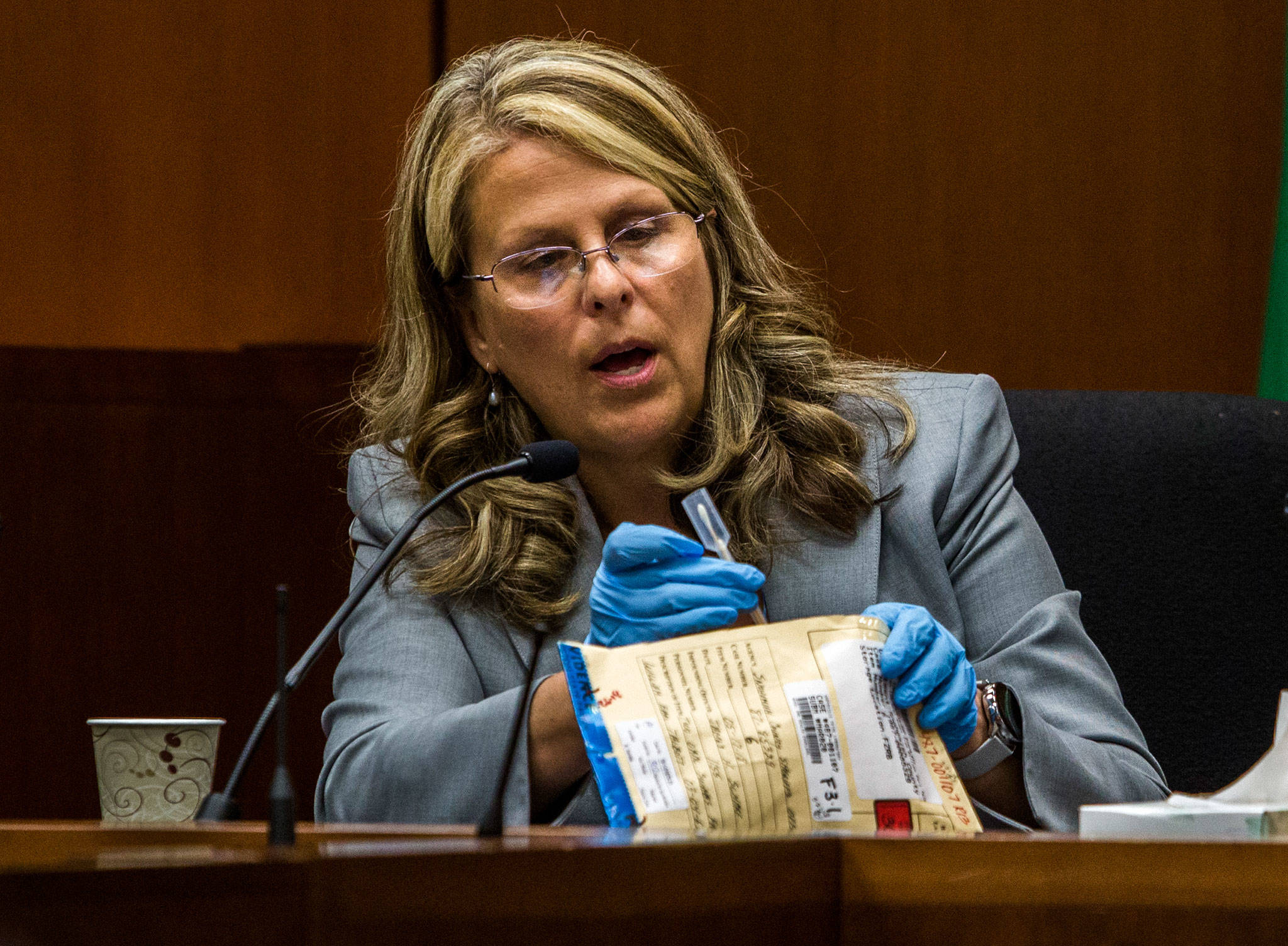Lisa Collins, a forensic scientist with the Washington State Patrol, looks at a swab used to collect DNA from William Talbott II during the trial of William Talbott II at the Snohomish County Courthouse on Monday in Everett. (Olivia Vanni / The Herald)