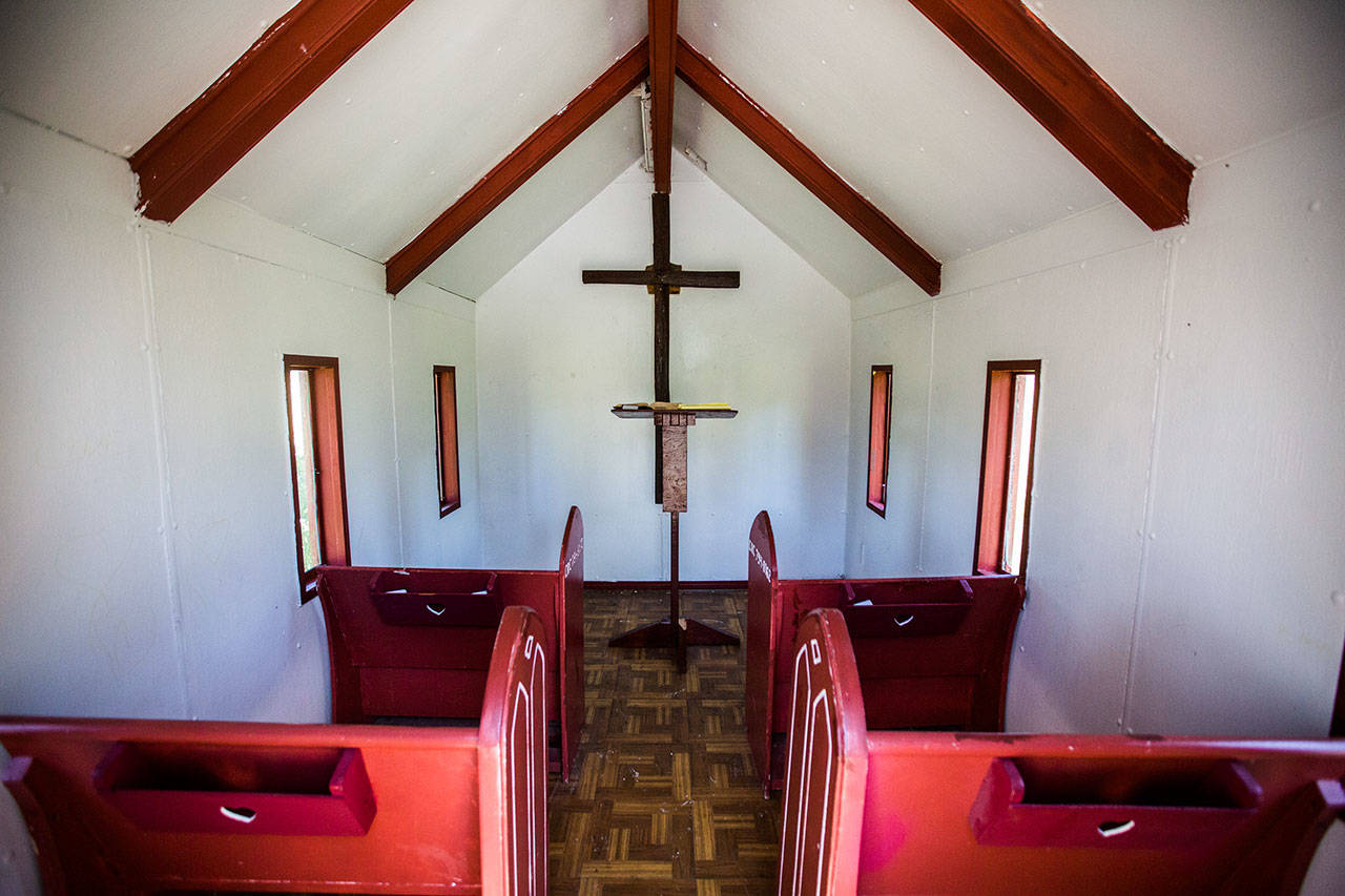 A white interior with four red pews at the Wayside Chapel on U.S. 2. (Olivia Vanni / The Herald)
