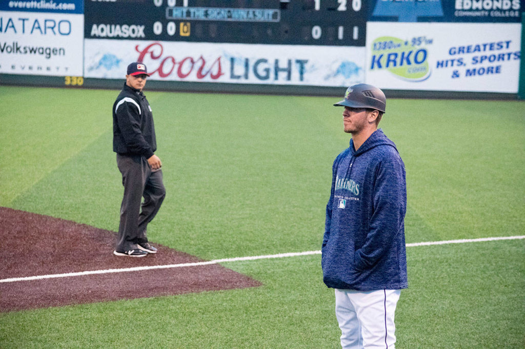 Cade Marlowe watches the game as he coaches first base for the AquaSox during a game against the Hawks on Tuesday at Funko Field at Everett Memorial Stadium. (Katie Webber / The Herald)