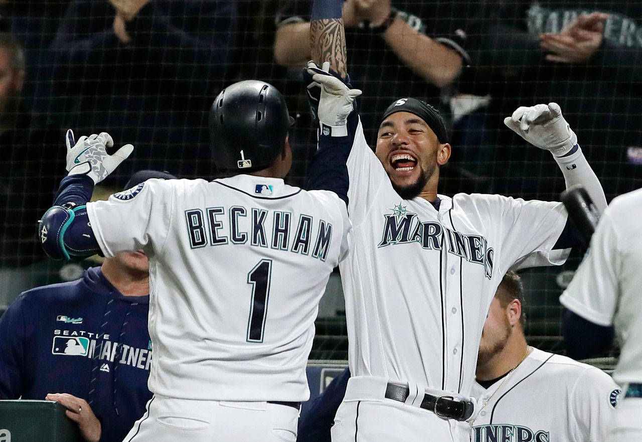 The Mariners' Tim Beckham (1) celebrates with J.P. Crawford (right) after Beckham hit a go-ahead solo home run during the eighth inning of a game against the Cardinals on July 2, 2019, in Seattle. (AP Photo/Ted S. Warren)