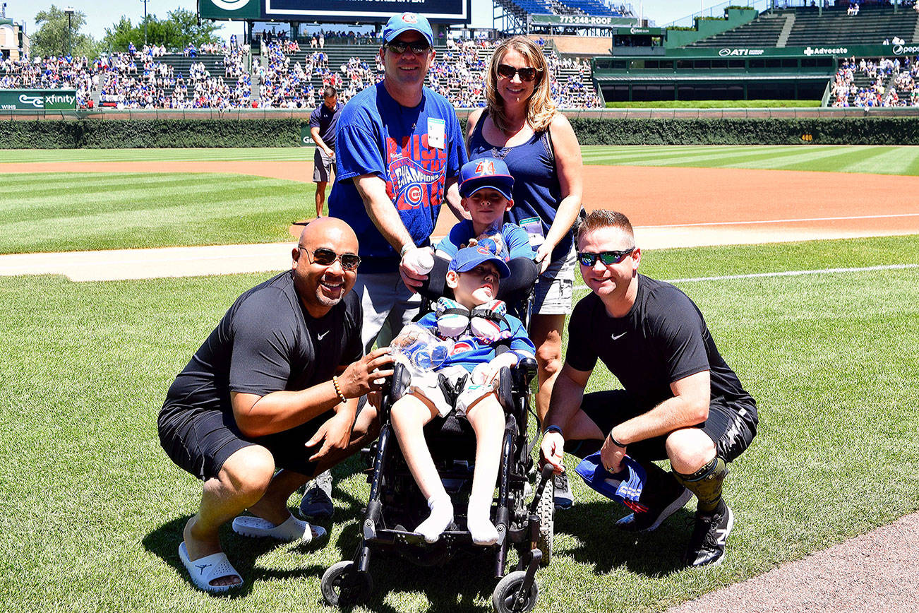 Umpire Mike Muchlinski of Snohomish (right) poses with a young fan and his family prior to a game at Wrigley Field. (Umps Care Charities)