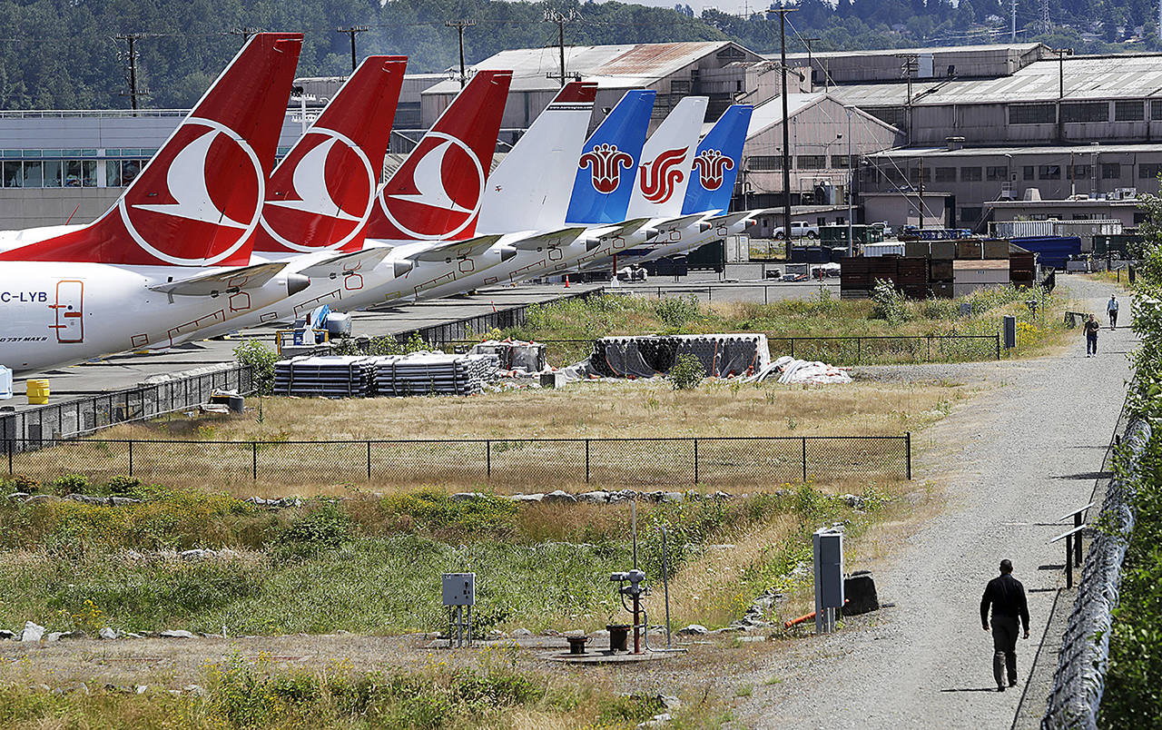 In this June 27 photo, people walk a trail past the tails of several of the dozens of grounded Boeing 737 MAX airplanes lining the edge of a parking area adjacent to Boeing Field in Seattle. (AP Photo/Elaine Thompson, File)