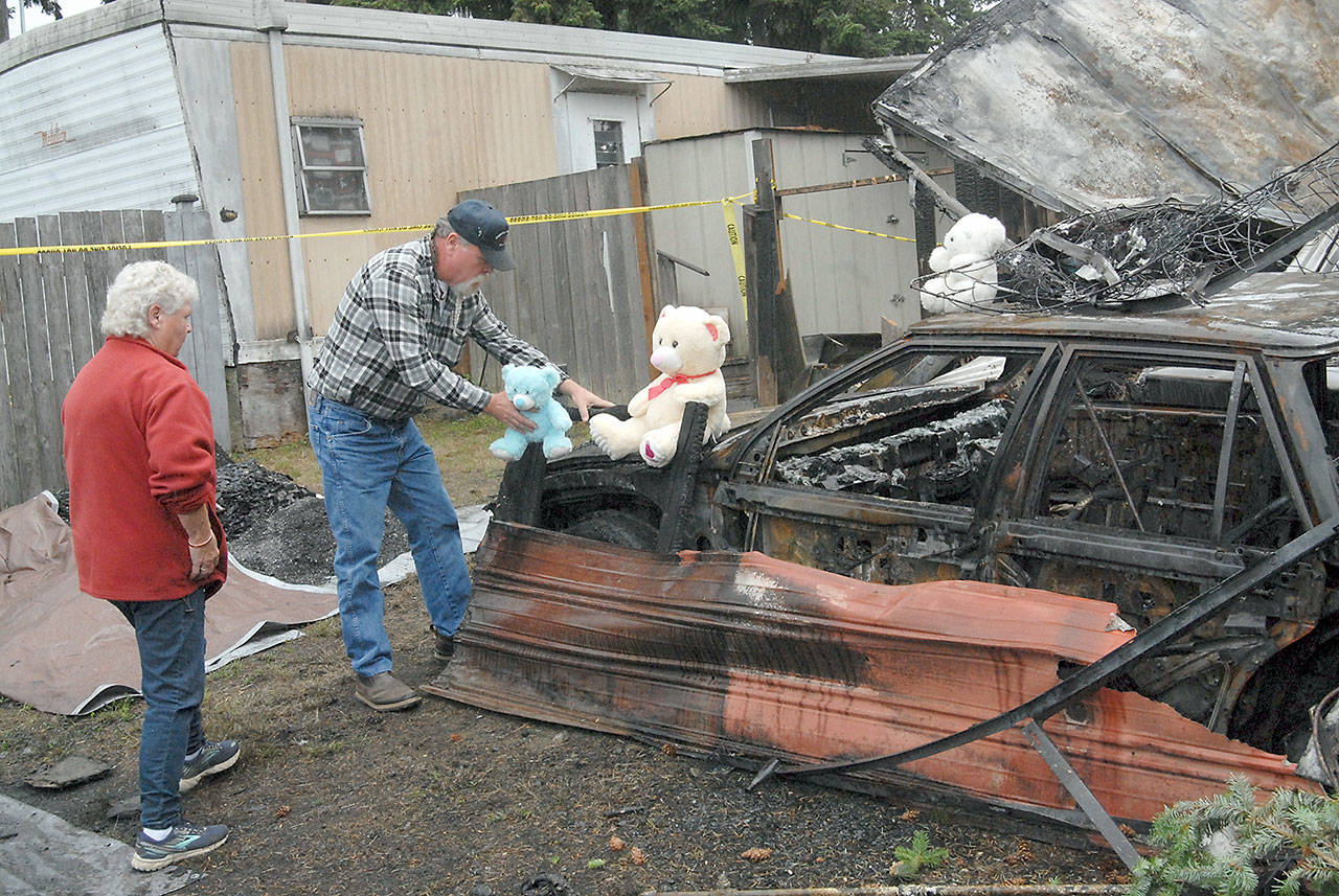 Jack Hutto of Port Angeles, grandfather to children Lilly Kambeitz, Emma Kambeitz and Jayden Kambeitz, accompanied by his mother, Pat Hutto, on Wednesday places teddy bears that belonged to his grandchildren next to the burned mobile home where the Kambeitz family was discovered after the house burned Saturday morning at the Welcome Inn RV Park in Port Angeles. (Keith Thorpe/Peninsula Daily News)
