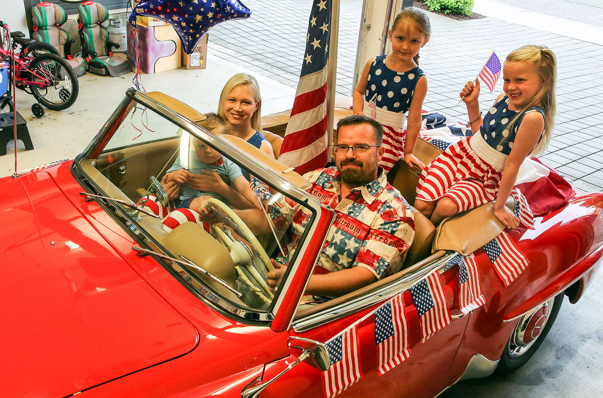 Olaf Wecker of Seattle offered up his red 1958 Mercedes 190SL convertible for the mayor's parade car in the Edmonds 4th of July parade. He is posed here with his wife, Christy, holding Walter, Karolin (left back) and Katrin (far right). (Kevin Clark / The Herald)