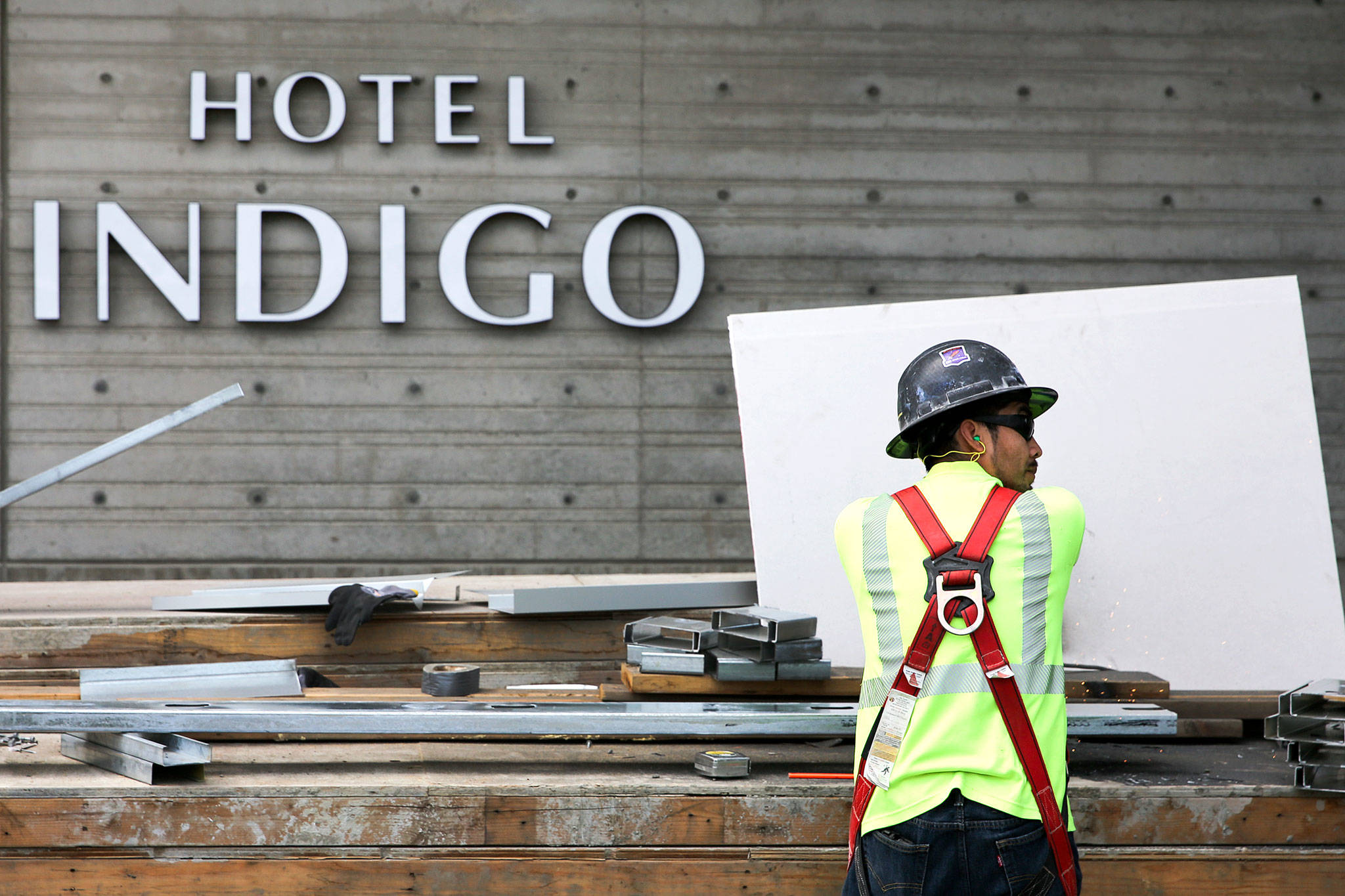 A construction crew member cuts steel at Hotel Indigo during construction on Port of Everett's Waterfront Place on June 26. (Kevin Clark / The Herald)