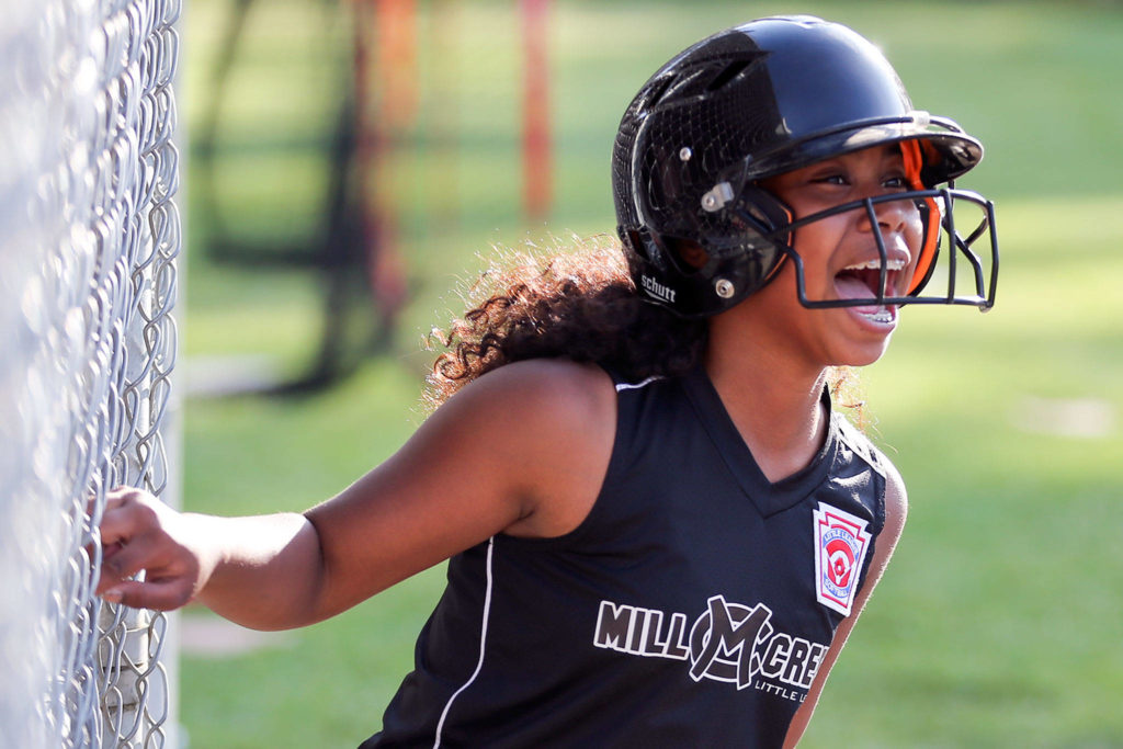 Mill Creek Little League's Elena Eigner celebrates during a drill on July 16 at Jackson High School in Mill Creek. (Kevin Clark / The Herald)