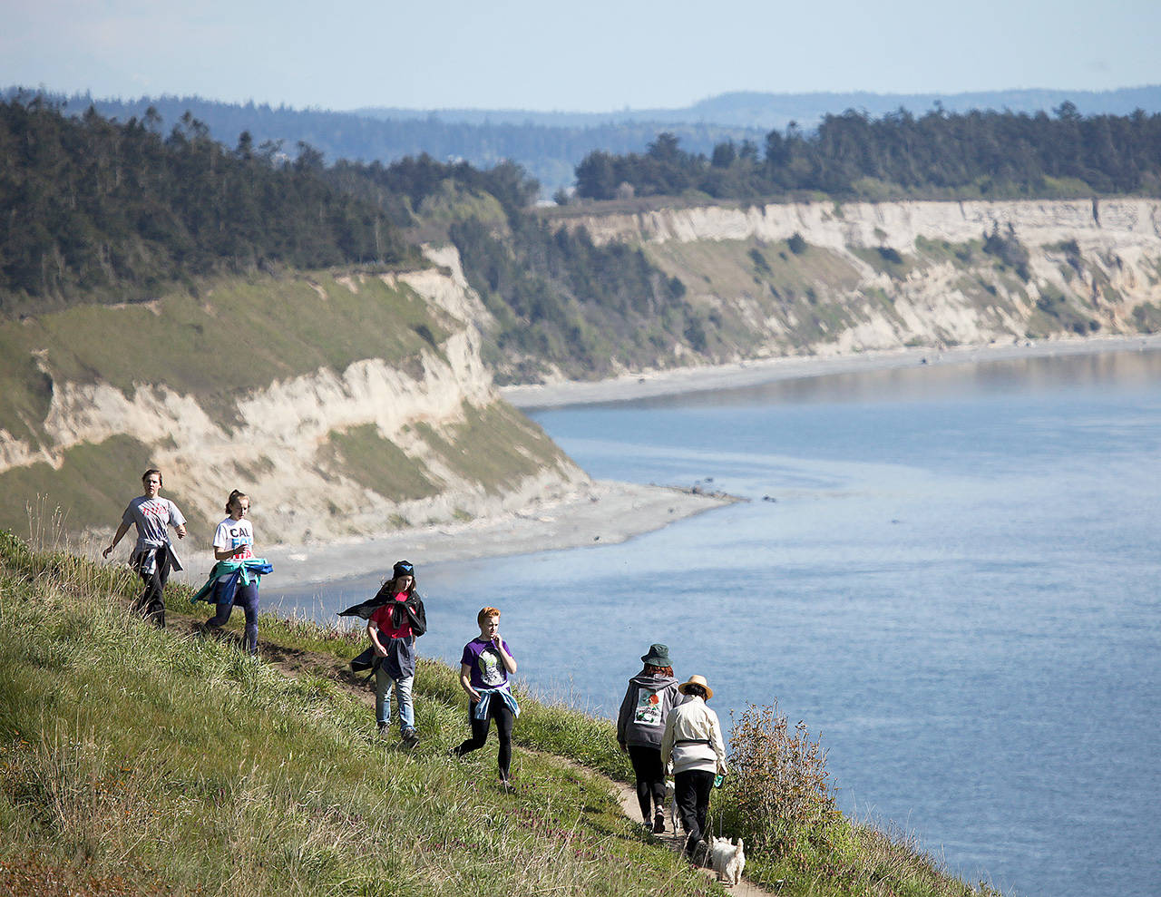 Hikers make their way along the Bluff Trail at Ebey's Landing near Coupeville on Whidbey Island. At its highest point, the bluff sits about 260 feet above sea level, providing stunning views of the Strait of Juan de Fuca and Olympic Mountains. (Ian Terry / Herald file)