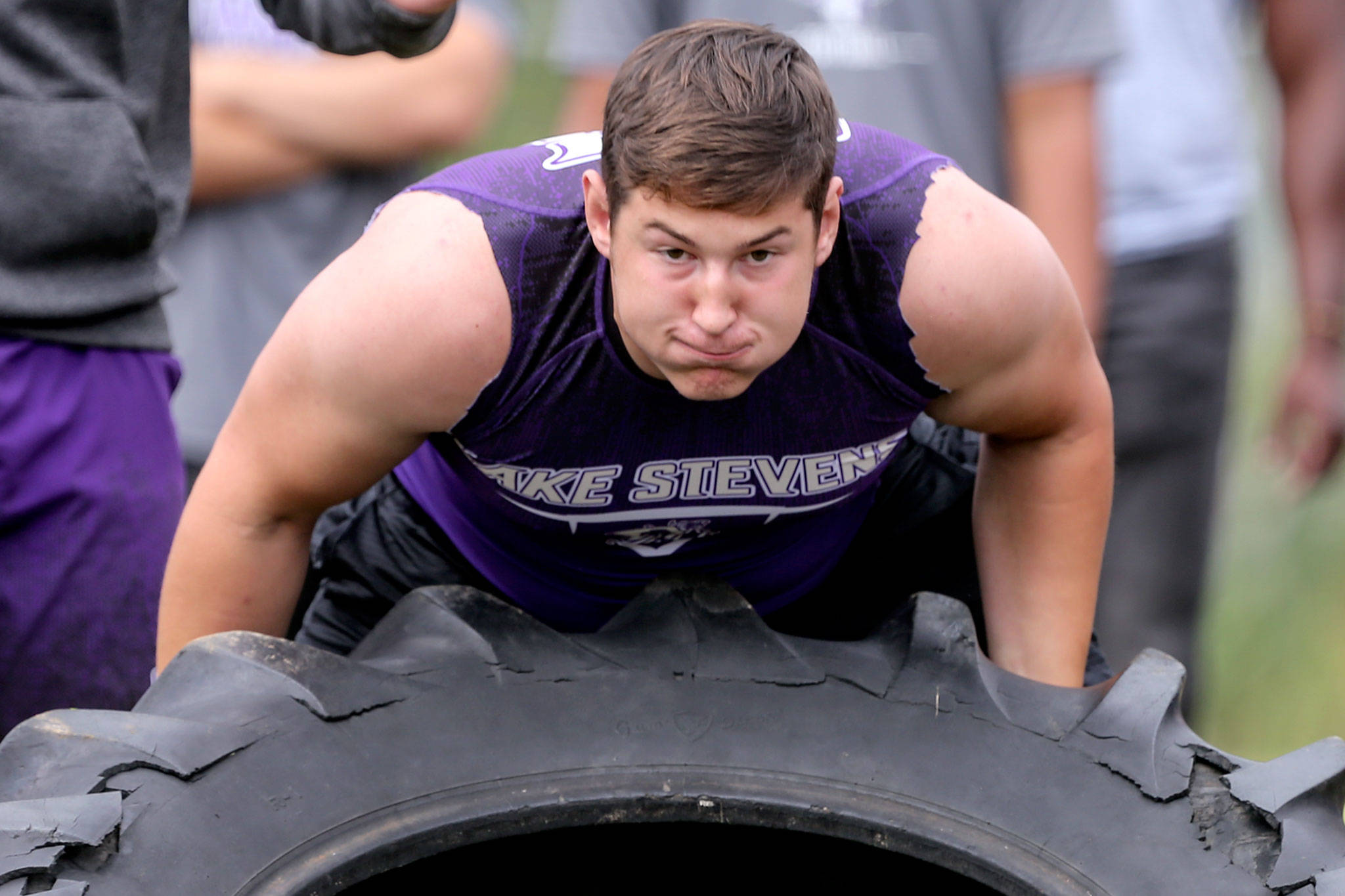Lake Stevens' Wyatt Hall races in the tire-flip relay as part of the lineman challenge. (Kevin Clark / The Herald)