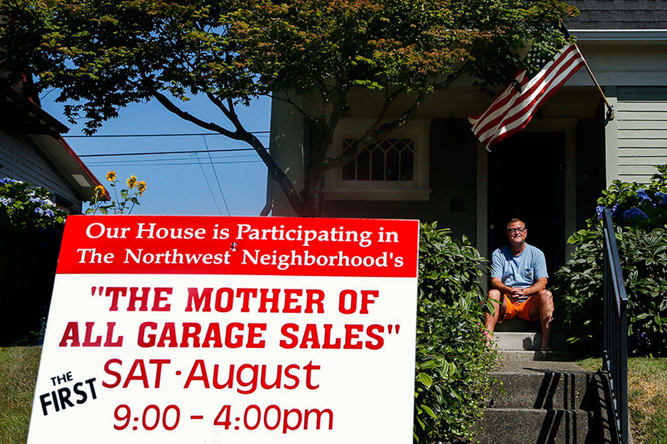 Behind a yard sign in his yard on Rucker Avenue, Bill Loesche takes a break from organizing movies, toys and micro machines he plans to sell Saturday at the Mother of All Garage Sales. (Dan Bates / The Herald)
