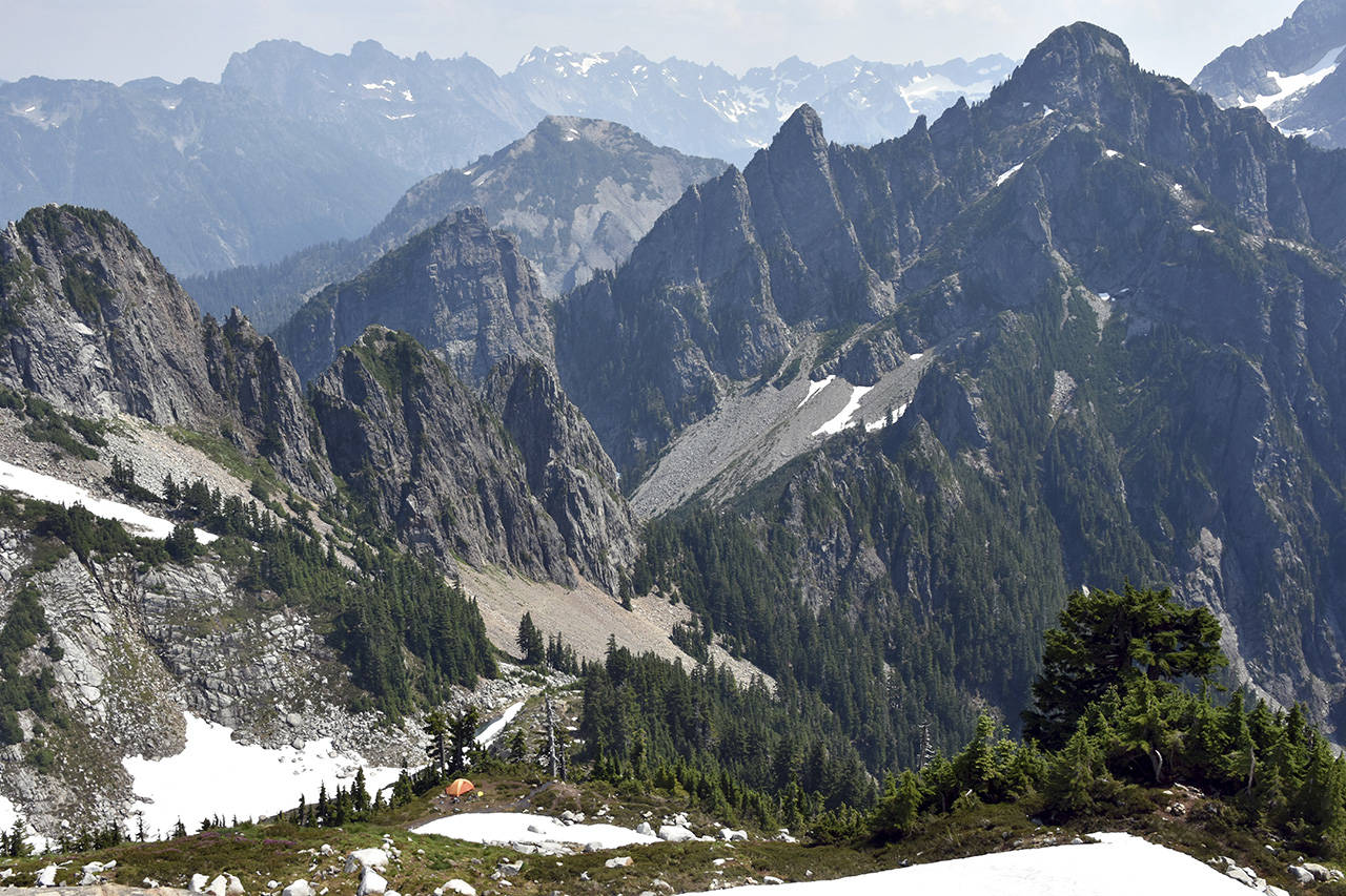 The view of east from Vesper Peak shows a climber's camp and Headlee Pass, at center, as well as the rugged terrain of the Glacier Peak Wilderness. (Caleb Hutton / The Herald)