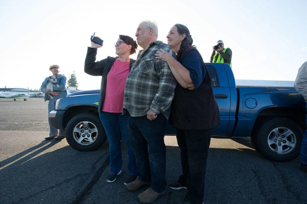 John Norman, his wife, Heather (right), and daughter Amber Nelson watch as his replica of the Spirit of St. Louis takes off on its first flight from Arlington Municipal Airport on July 28. (Andy Bronson / The Herald)