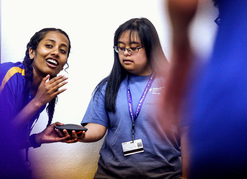 Margot Amalachandran, 21, a unit leader at Camp Prov, helps Bre Baylon with a speaker that blasts camp songs during activity time in Lions Hall at Forest Park on Wednesday. (Dan Bates / The Herald)