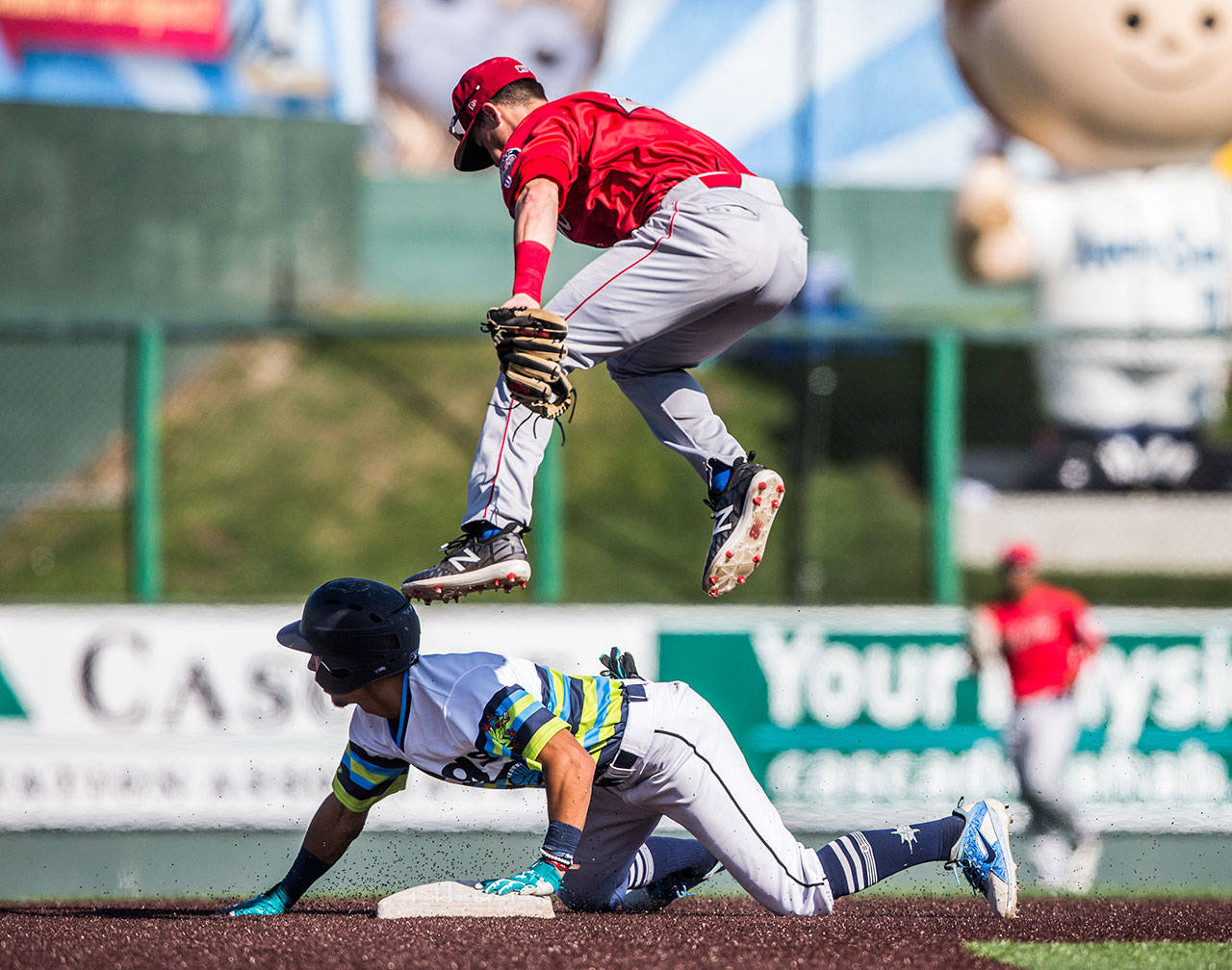 Spokane's Jake Hoover jumps over Everett's Cesar Izturis Jr. as he slides into second during the AquaSox 7-6, 10-inning victory over Spokane on Sunday at Funko Field in Everett. (Olivia Vanni / The Herald)
