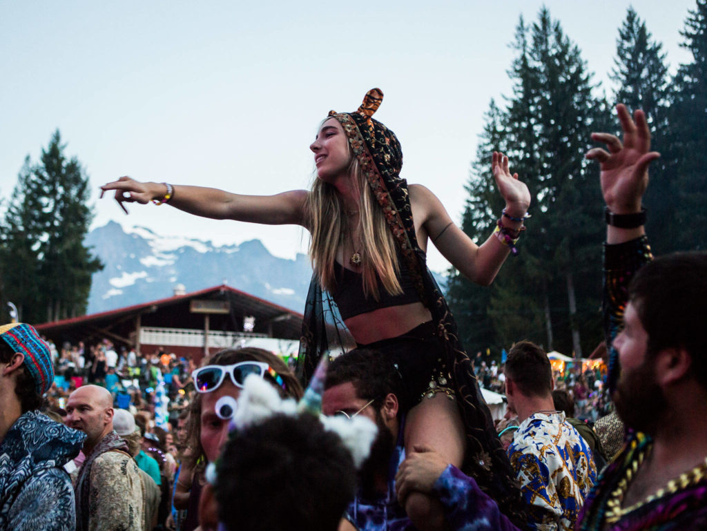 A festival goer dances on someone shoulders during The Polish Ambassador the third day of Summer Meltdown on Saturday, Aug. 3, 2019 in Darrington, Wash. (Olivia Vanni / The Herald)