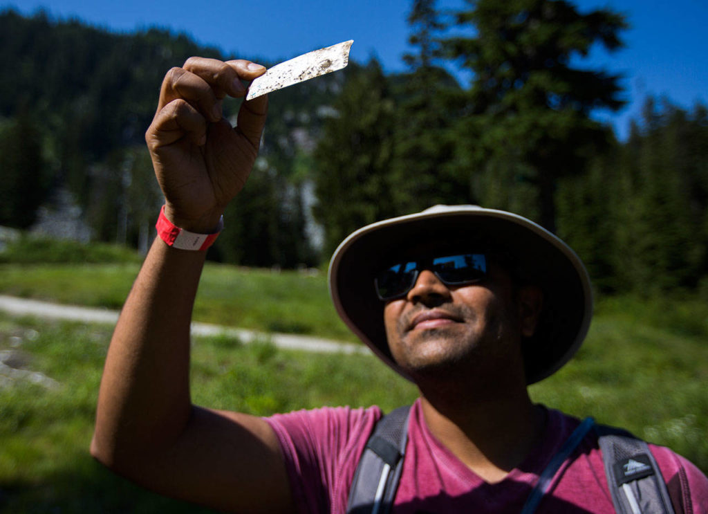 Sanjog Patel holds an old and faded ski pass he found during the annual Stevens Pass cleanup. (Olivia Vanni / The Herald)