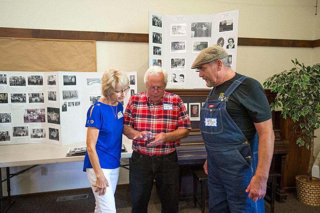 Gary Jackson shows photos to Robin Monson Sather (left) and his brother Dale (right) during a reunion on Thursday of former students who attended the Silvana School. (Andy Bronson / The Herald)