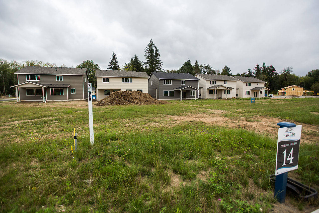 Newly constructed Cascade Breeze homes sit next undeveloped lots as a new home is constructed in the background on Thursday in Sultan. (Olivia Vanni / The Herald)