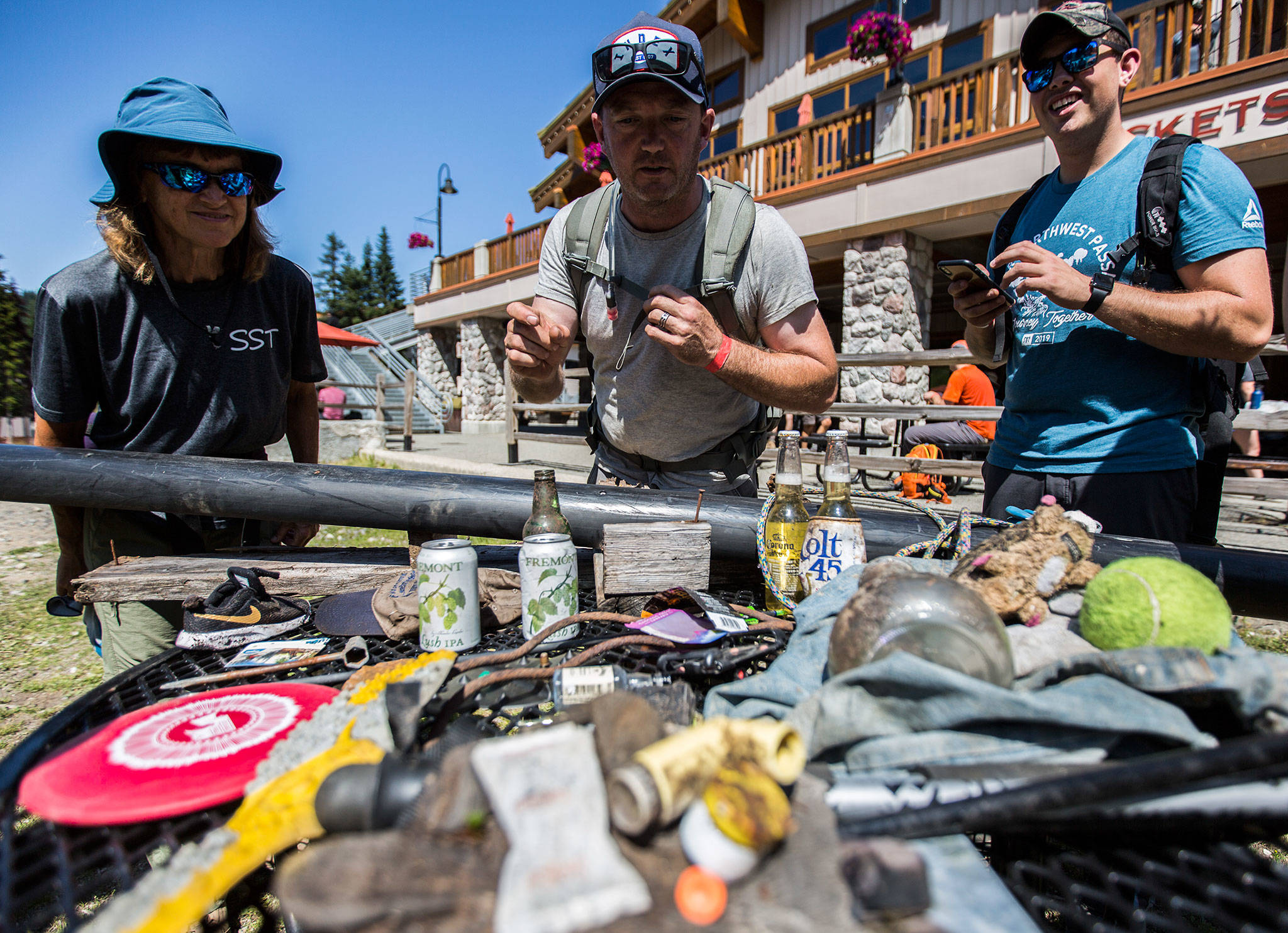 Volunteers survey some of the items they found — including unopened beers and a medical inhaler — during the annual trash pick-up at Stevens Pass on Aug. 7. (Olivia Vanni / The Herald)
