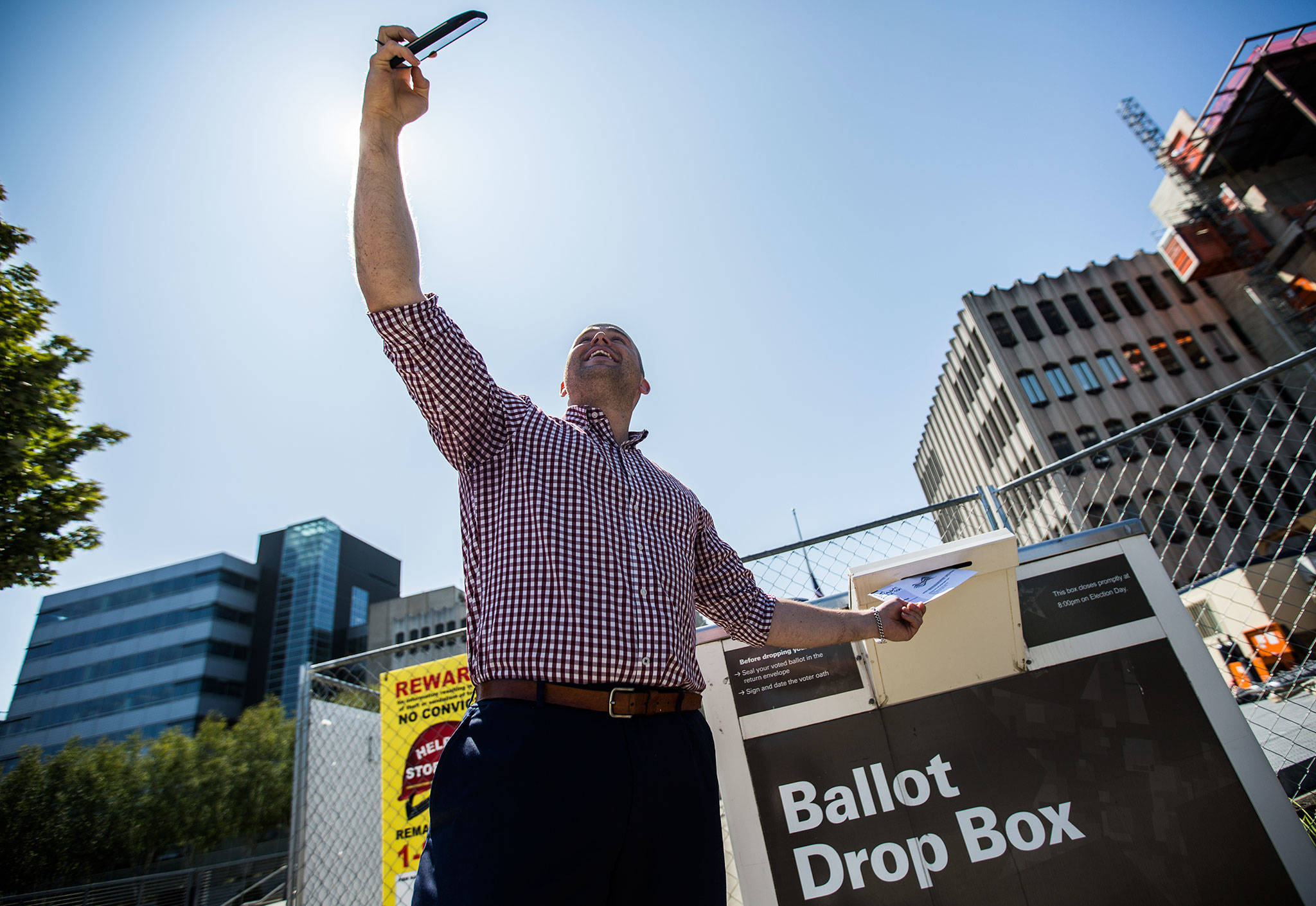 Snohomish County Council District 2 candidate Alex Lark stops to take a photo before dropping his ballot in the box on the Snohomish County Campus Plaza on Aug. 6 in Everett. (Olivia Vanni / The Herald)