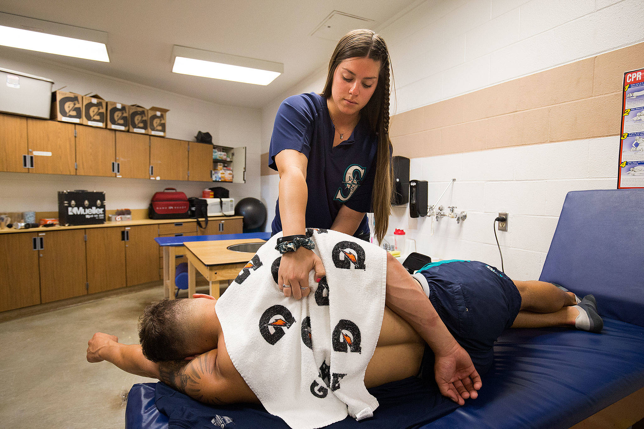 AquaSox athletic trainer Amanda Lee works on a player's shoulder in the training room of the team's clubhouse Aug. 13 in Everett. (Andy Bronson / The Herald)