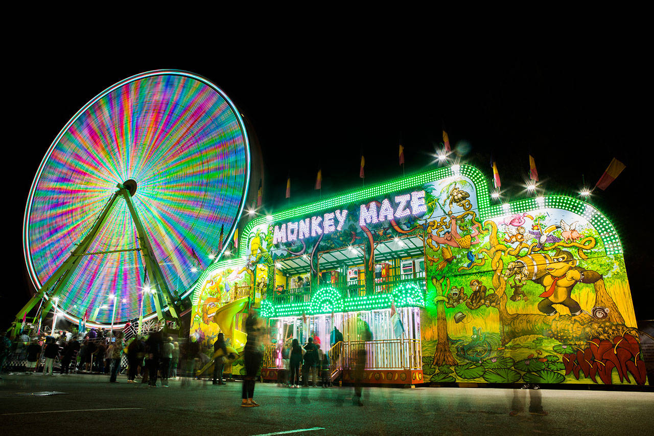 The carnival at the Evergreen State Fair glows at night in 2018. (Olivia Vanni / The Herald)