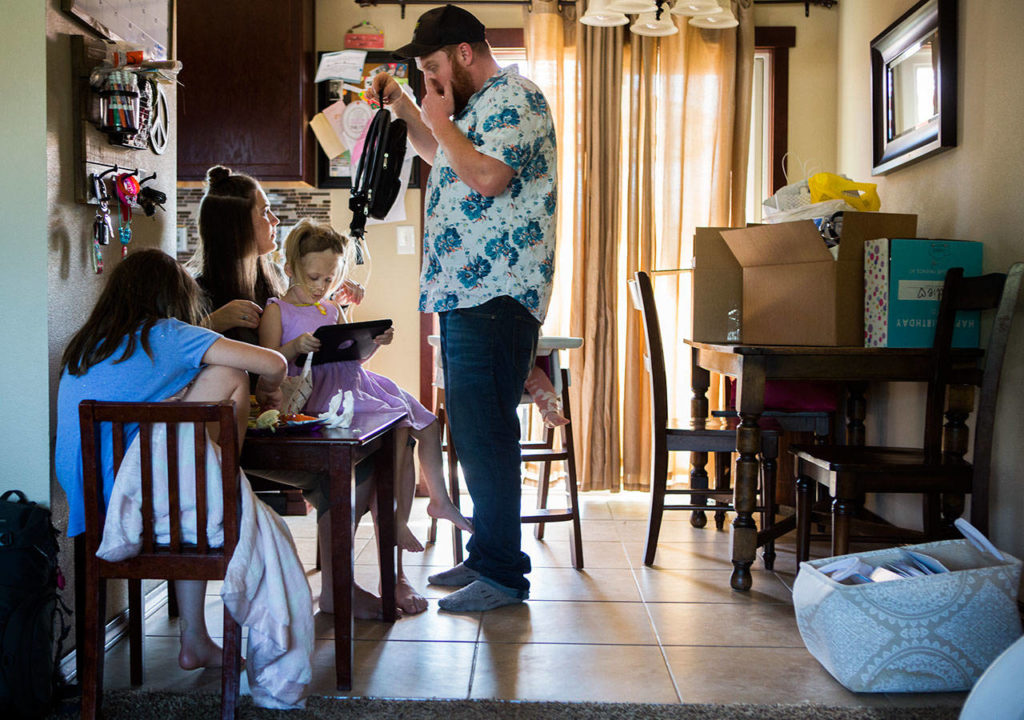 Sadie Sheldon sits on her mother Erin Sheldon's lap, and her father, Kellen Sheldon, helps adjust her feeding-tube backpack while the family eats lunch. (Olivia Vanni / The Herald)
