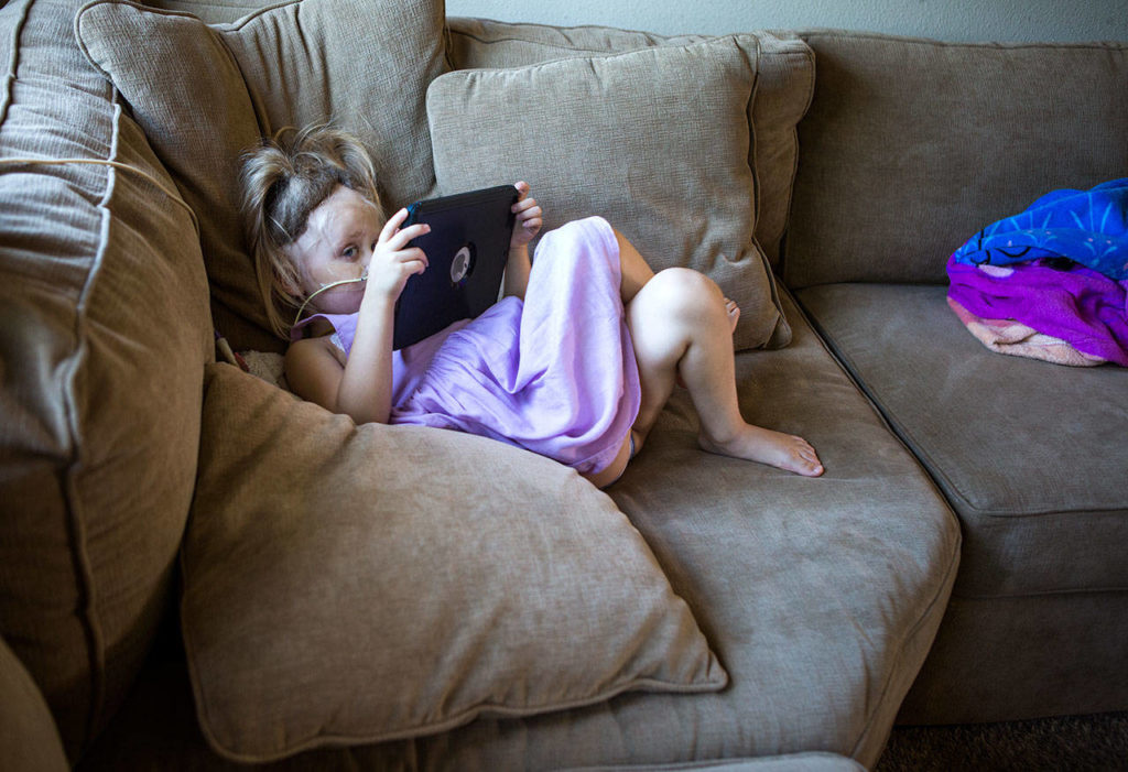Sadie relaxes on the couch with her iPad. (Olivia Vanni / The Herald)