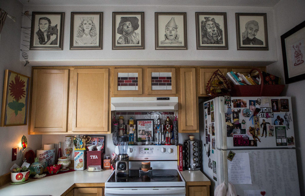Wizard of Oz character sketches picked up by a family member hang on the wall over her kitchen which is also filled with Wizard of Oz items on Friday, Aug. 16, 2019 in Granite Falls, Wash. (Olivia Vanni / The Herald)