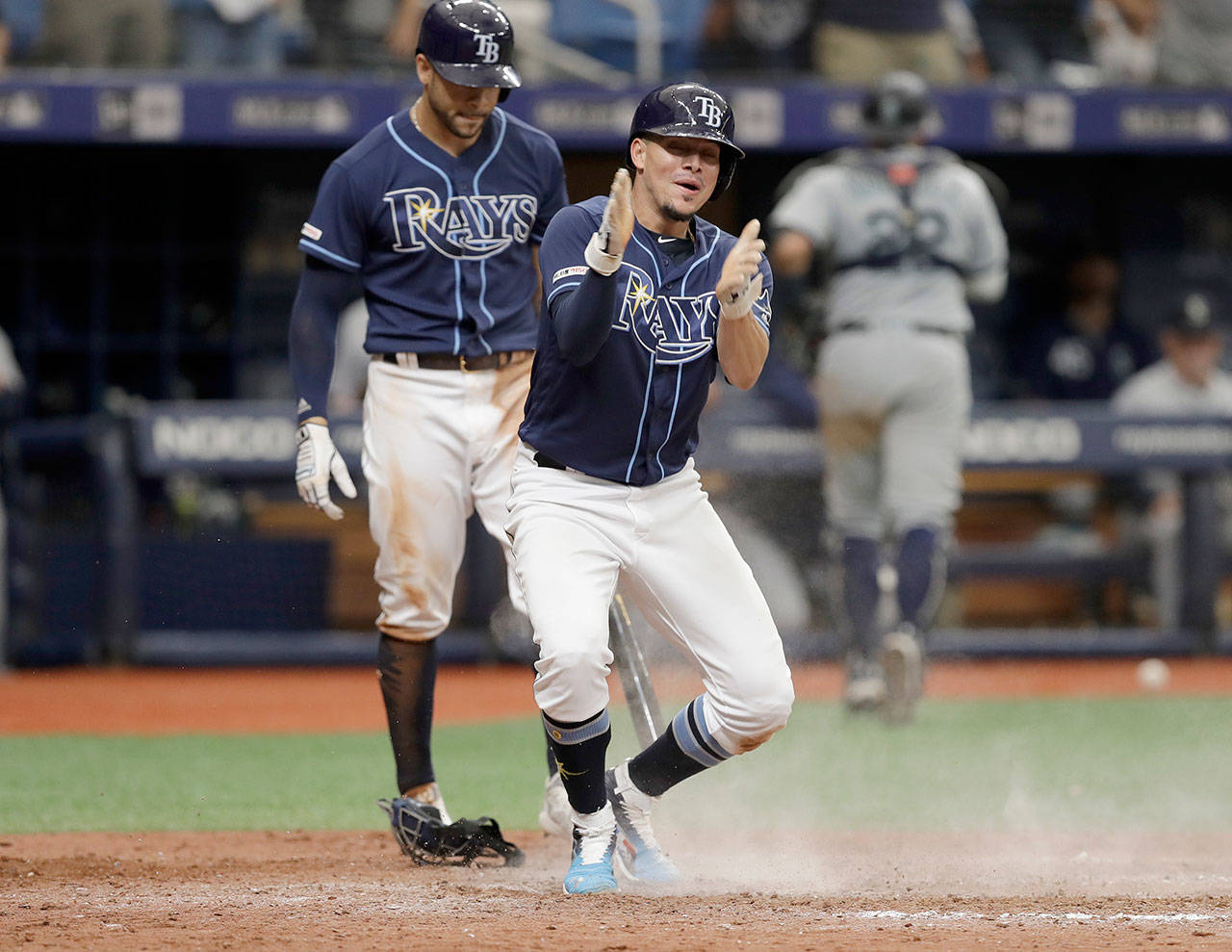 Tampa Bay's Willy Adames (front) reacts to scoring the game-winning run on a wild pitch by Seattle's Matt Magill during the ninth inning Wednesday in St. Petersburg, Florida, as Tommy Pham looks on. (AP Photo/Chris O'Meara)