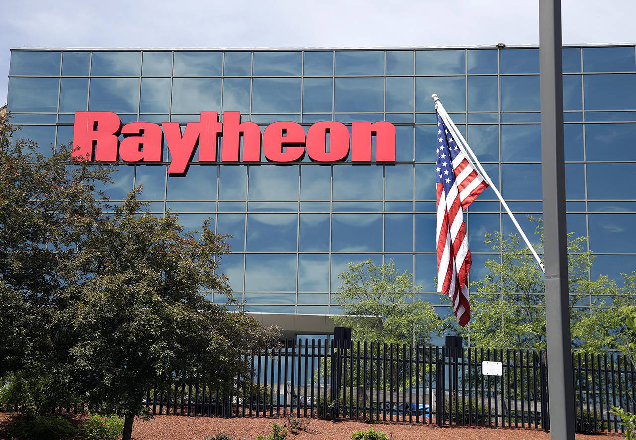 A flag flies in front of the facade of Raytheon's Integrated Defense Systems facility June 10 in Woburn, Massachusetts. (AP Photo/Elise Amendola)