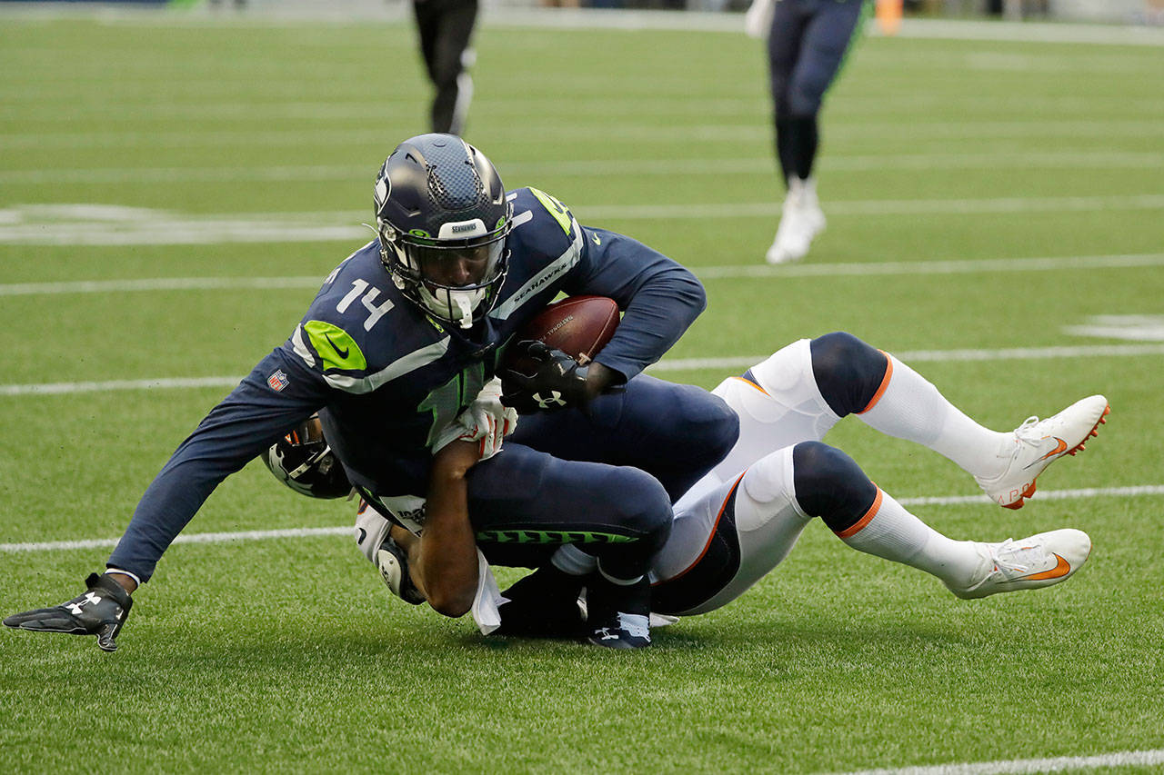 Seahawks wide receiver DK Metcalf (14) is tackled by Broncos cornerback Chris Harris after making a catch during the first half of a preseason game on Aug. 8, 2019, in Seattle. (AP Photo/Elaine Thompson)