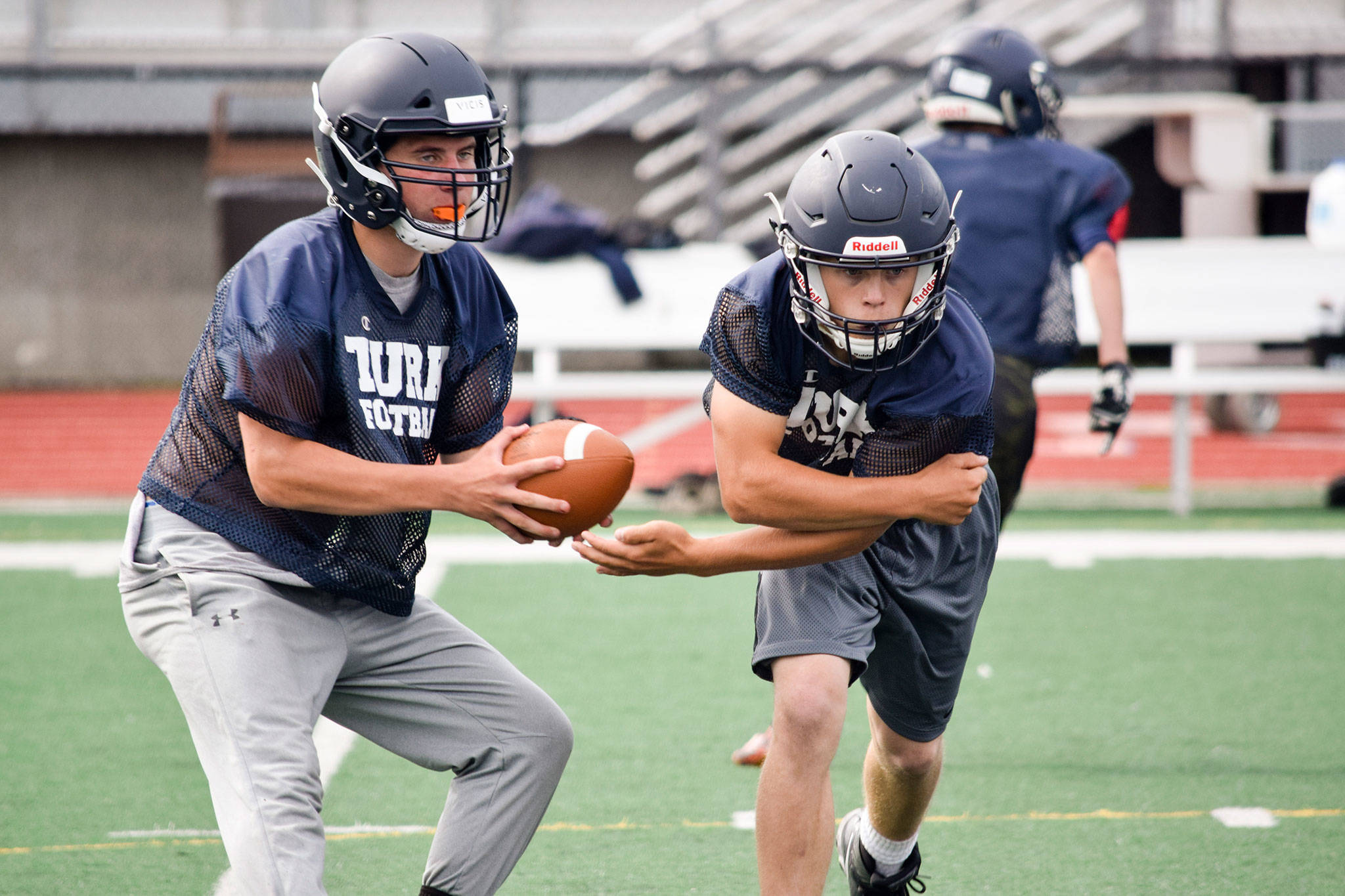 Sultan senior quarterback Willy Bennett fakes a hand-off to senior running back Aidan Fleming during practice on Aug. 23, 2019, at Sultan High School. (Katie Webber / The Herald)
