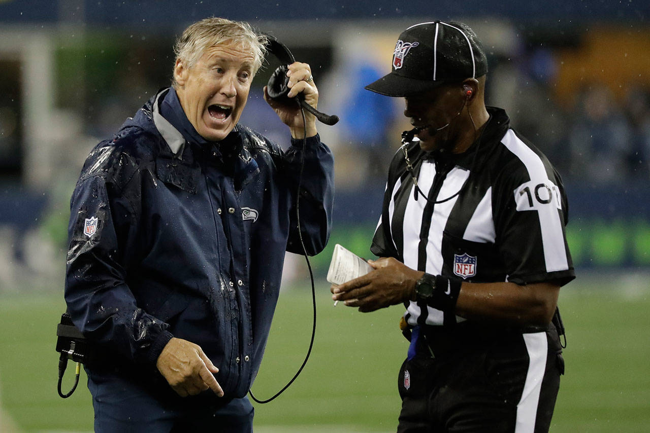 Seahawks head coach Pete Carroll (left) talks with line judge Carl Johnson during the first half of a preseason game against the Raiders on Aug. 29, 2019, in Seattle. (AP Photo/Elaine Thompson)