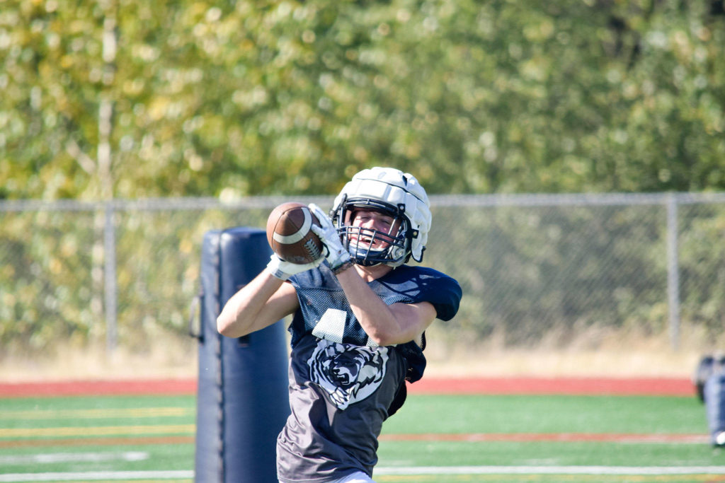 Junior Trevor Meldrom catches the ball while practicing offensive plays during football practice on Aug. 27, 2019, at Glacier Peak High School in Snohomish. (Katie Webber / The Herald)