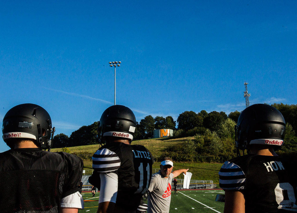 Players listen to plays calls from the sidelines during football practice at Monroe High School on Wednesday, Aug. 28, 2019 in Monroe, Wash. (Olivia Vanni / The Herald)