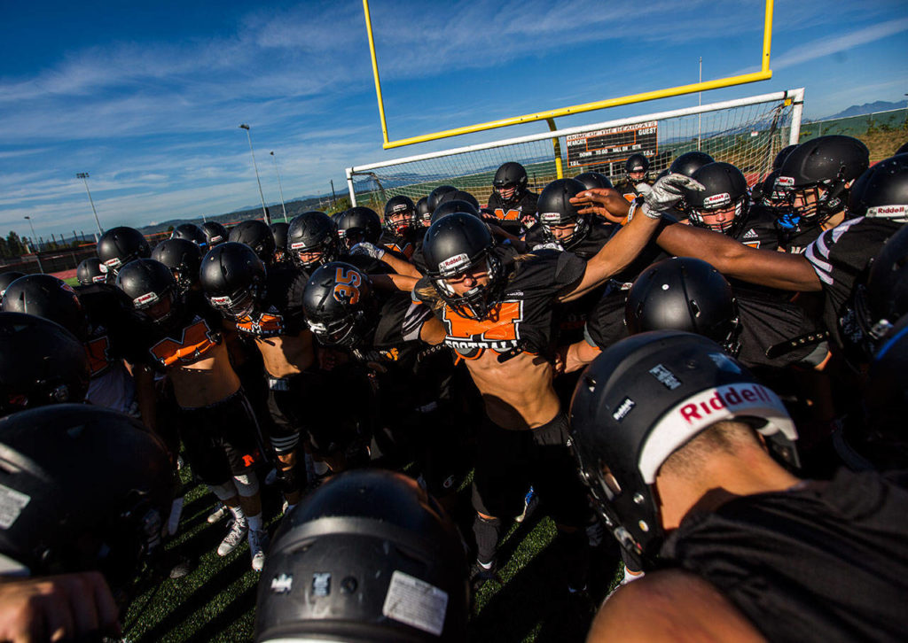 The Monroe High School football team gets together in a huddle before the start of football practice on Wednesday, Aug. 28, 2019 in Monroe, Wash. (Olivia Vanni / The Herald)