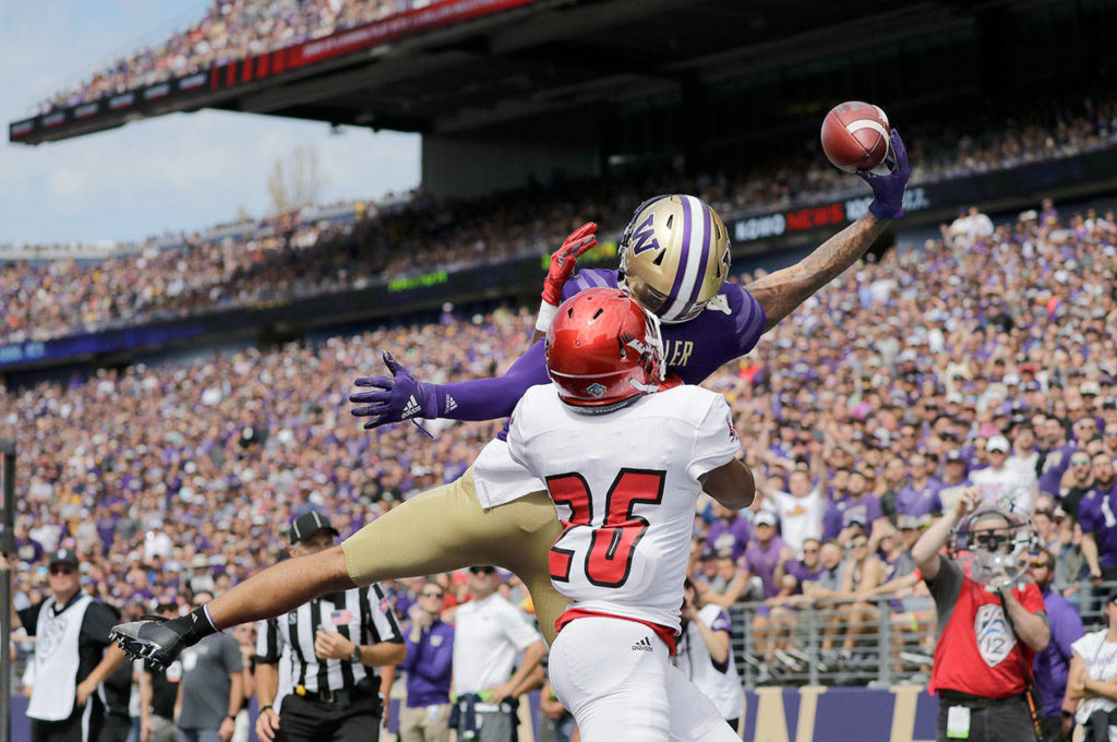 Washington's Aaron Fuller makes a one-handed catch for a touchdown over Eastern Washington's Darreon Moore (26) in the first half of the NCAA college football game Saturday in Seattle. (AP Photo/Elaine Thompson)