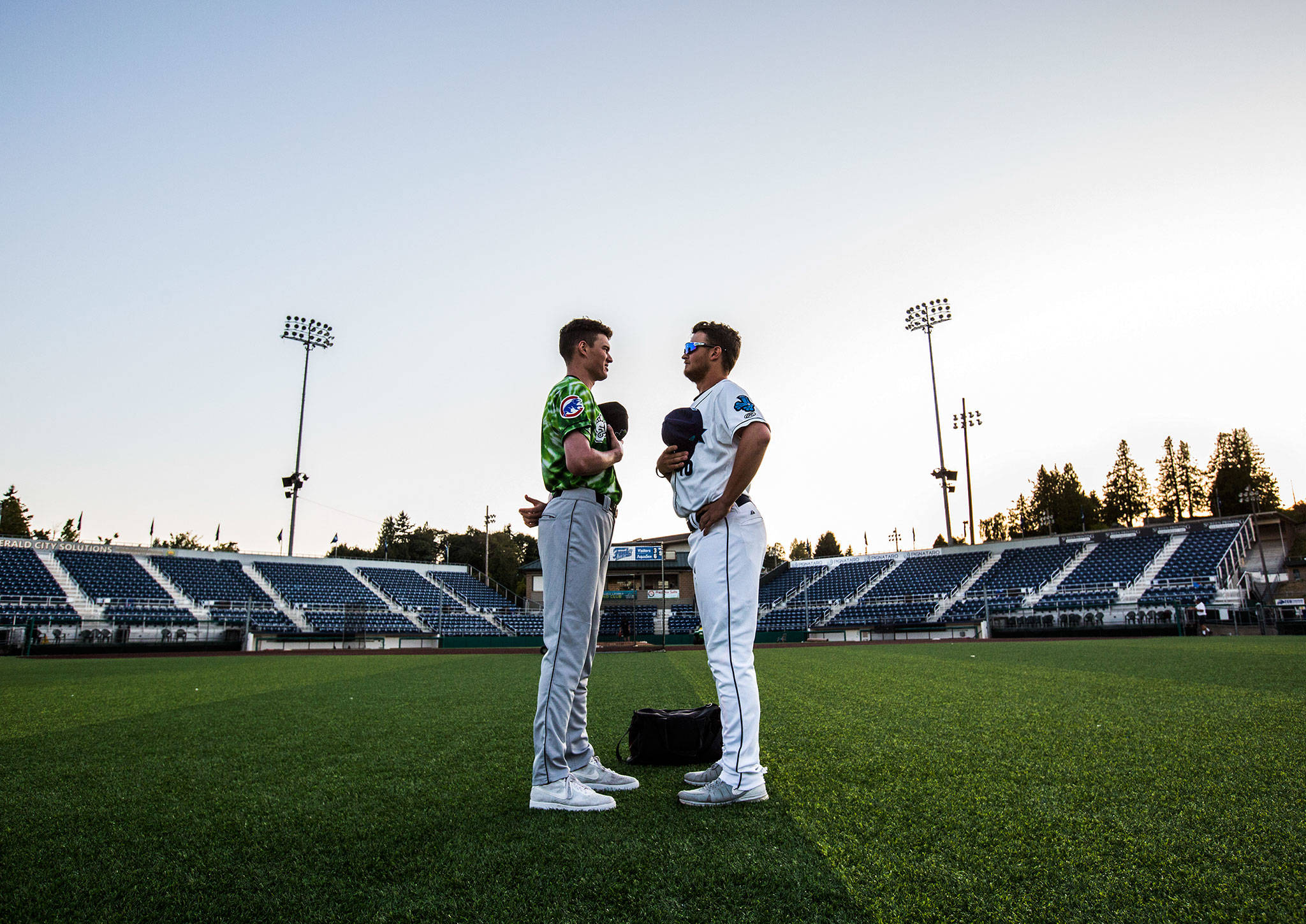 AquaSox's Travis Kuhn and Emerald's Ryan Jensen were still standing an hour after the game between the two teams Aug. 25 in salute to the National Anthem at Funko Field in Everett. (Olivia Vanni / The Herald) (Olivia Vanni / The Herald)