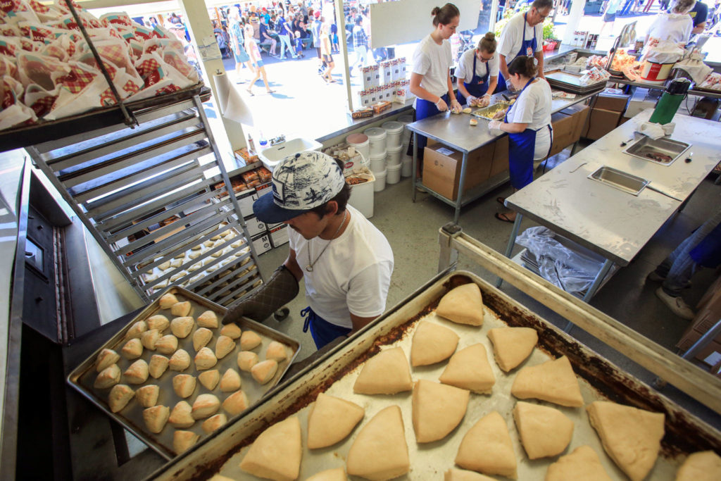 Cisco Martinez unloads fresh scones at the Fisher Scones booth at the Evergreen State Fair. (Kevin Clark / Herald file)
