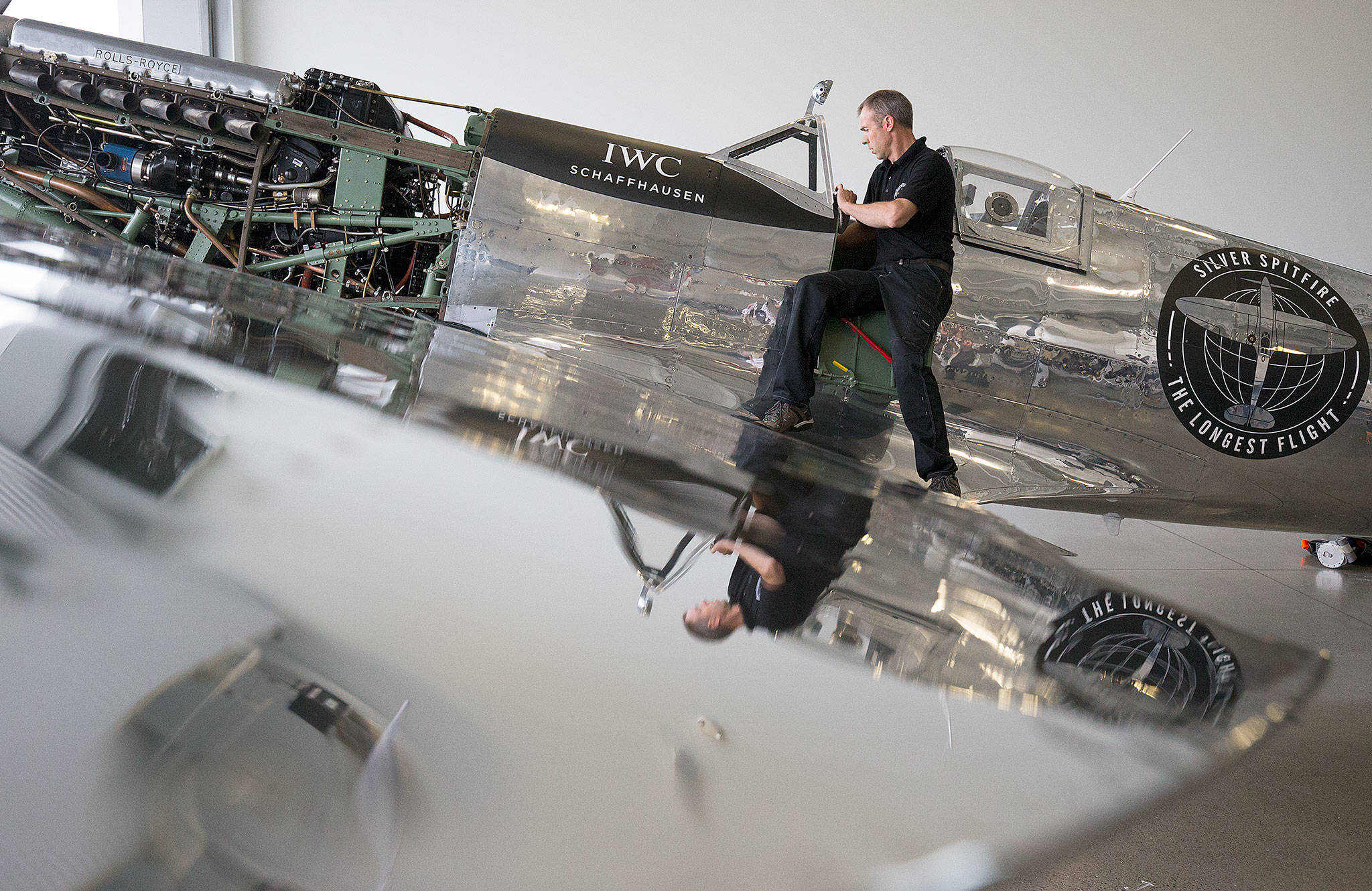 Reflected in the polished aluminum wing, Chief Engineer Martin Overall reaches into the cockpit of the Silver Spitfire, a World War II Supermarine Spitfire Mk.IX fighter plane, during a 50-hour maintenance checkup at the Historic Flight Foundation on Wednesday in Mukilteo. (Andy Bronson / The Herald)