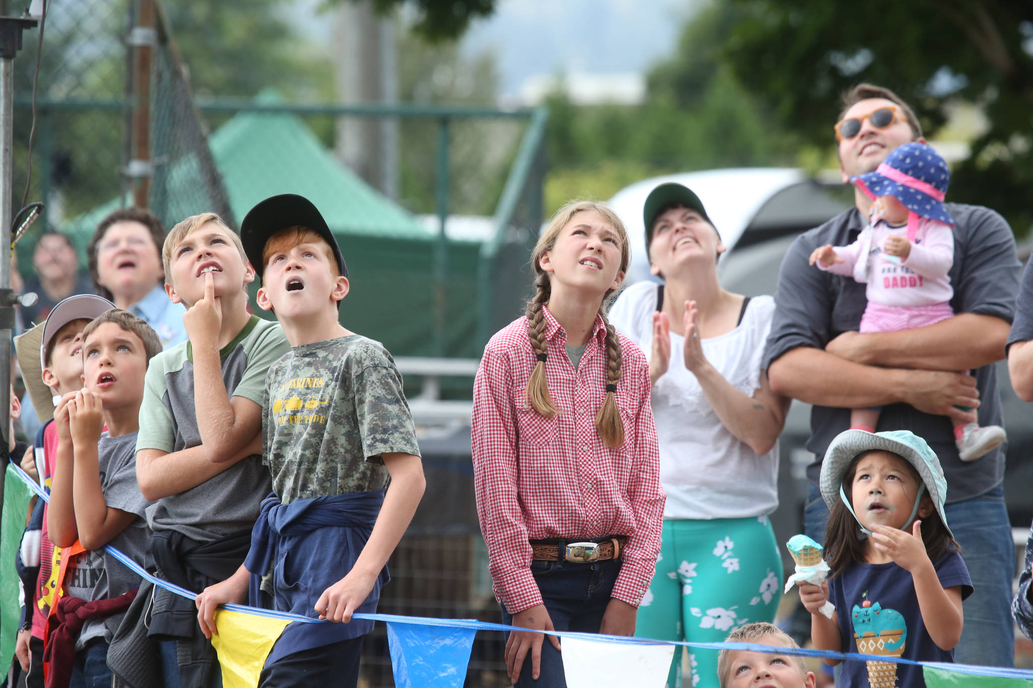 Kids watch as loggers climb 60 foot poles during the International Lumberjack Show on opening day of the Evergreen State Fair on Aug. 22 in Monroe. (Andy Bronson / The Herald)