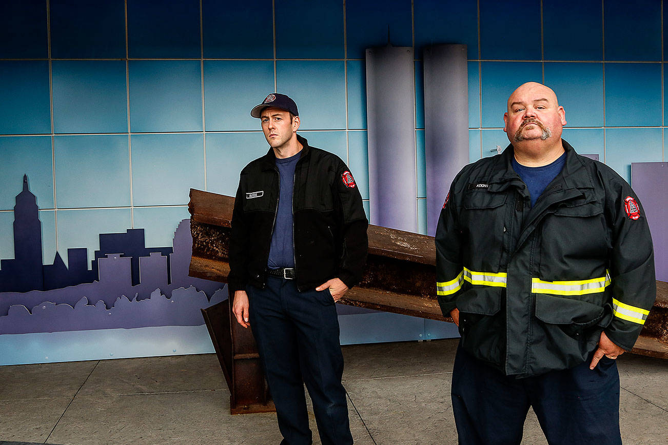 Arlington firefighter Aaron Boede, 30 (left), and acting Capt. Greg Koontz with a steel beam that was recovered from ground zero after the attacks of Sept. 11, 2001. A memorial display at Arlington's Fire Station 46 is visible from the street and open to the public. (Dan Bates / The Herald)