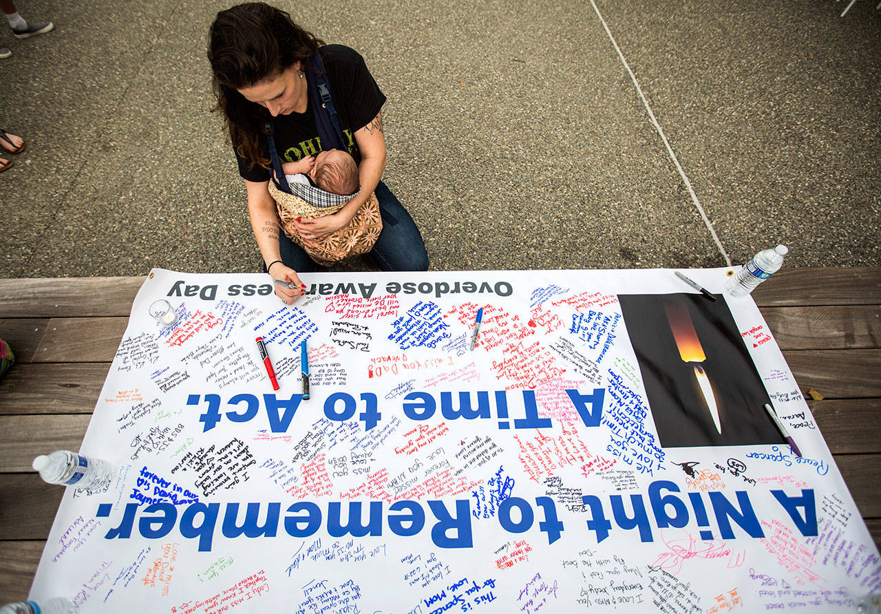 Johanna Sellers holds her son Amado, 6 weeks, who is named after a friend who died of a drug overdose, whole signing a banner during Snohomish Overdose Prevention's A Night to Remember on Thursday in Everett. (Olivia Vanni / The Herald)