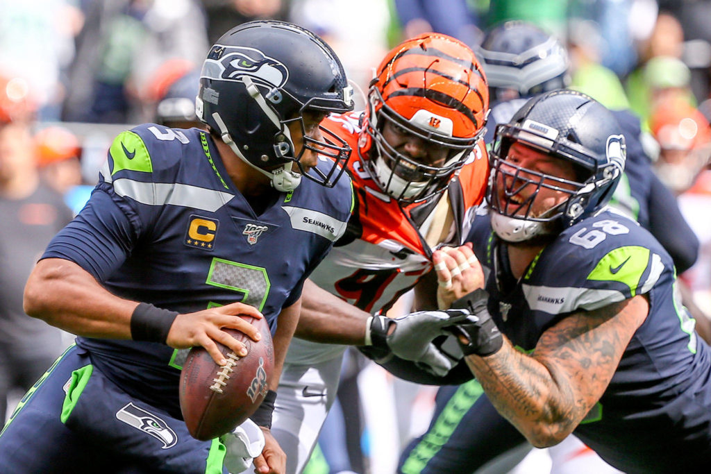 Seattle's Russell Wilson is chased out of the pocket by Cincinnati's Geno Atkins with Justin Britt at CenturyLink Field Sunday afternoon in Seattle on September 8, 2019. The Seahawks won 21-20. (Kevin Clark / The Herald)