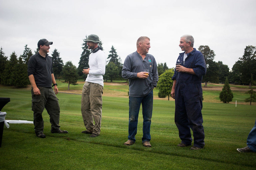 Members of Legion Memorial Golf Course's grounds crew talk before a dedication ceremony near the tee box on the 14th hole Wednesday in Everett. (Andy Bronson / The Herald)