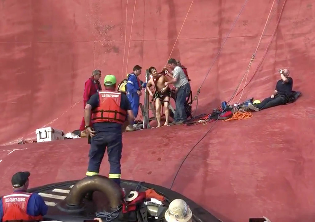 In this image taken from video Monday, Coast Guard rescuers assist one of four men who were trapped in a capsized ship off Jekyll Island, Georgia, drilling into the hull's steel plates to extract them more than a day after their vessel overturned. (U.S. Coast Guard via AP)