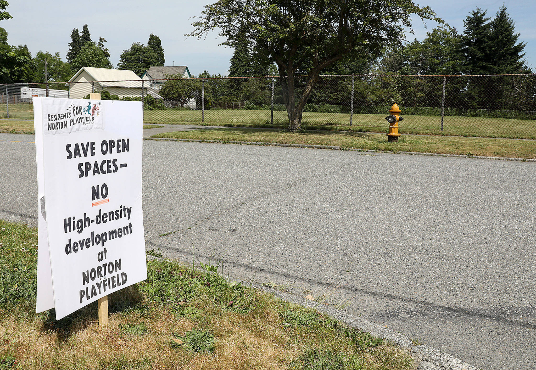 Signs have popped up in the Port Gardner neighborhood against a proposal by the Everett School District and Housing Hope to build affordable housing on a playfield on Norton Avenue. (Lizz Giordano / The Herald)