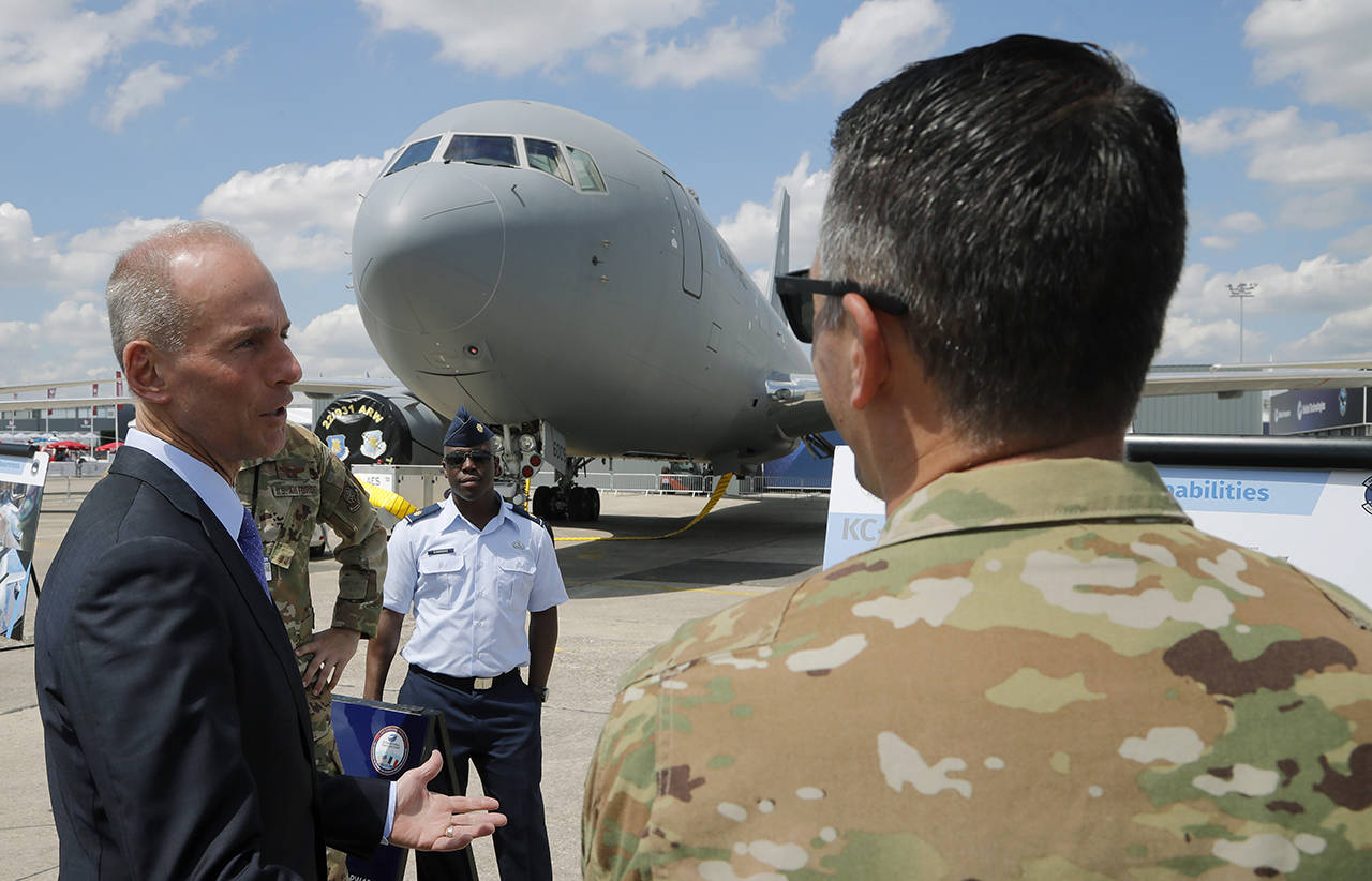 Boeing Chief Executive Dennis Muilenburg speaks to a crew member of a Boeing KC-46 taker at the Paris Air Show, in Le Bourget, east of Paris, France, on June 17. (AP Photo/Michel Euler, file)