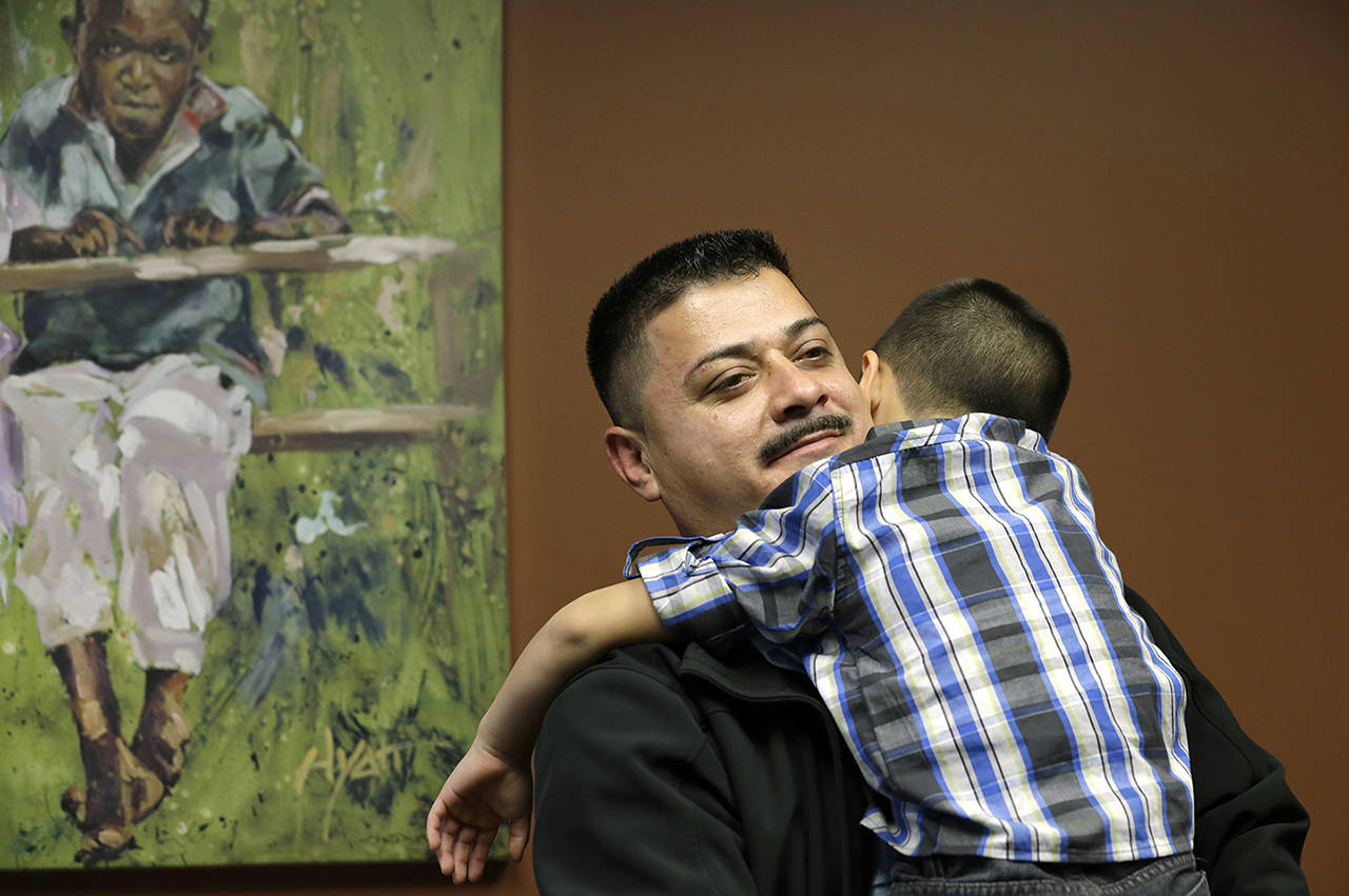In this 2014 photo, Ignacio Lanuza-Torres holds his son, Isaiah, 4, during a portrait session in Seattle. Lanuza-Torres was nearly deported after a U.S. Immigration and Customs Enforcement lawyer forged a key document in his case. (AP Photo/Elaine Thompson, File)